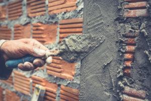 Um trabalhador construindo paredes e tijolos